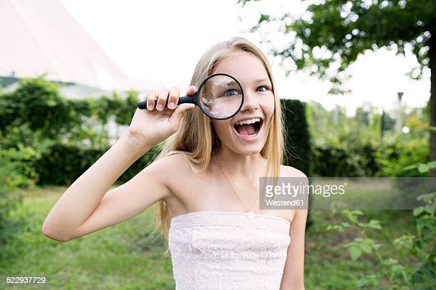 Girl looking through magnifying glass