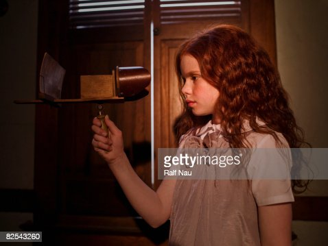 Girl looking through old-fashioned 3-D device : Stock Photo