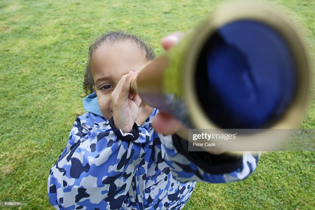 Girl looking through telescope : Stock Photo
