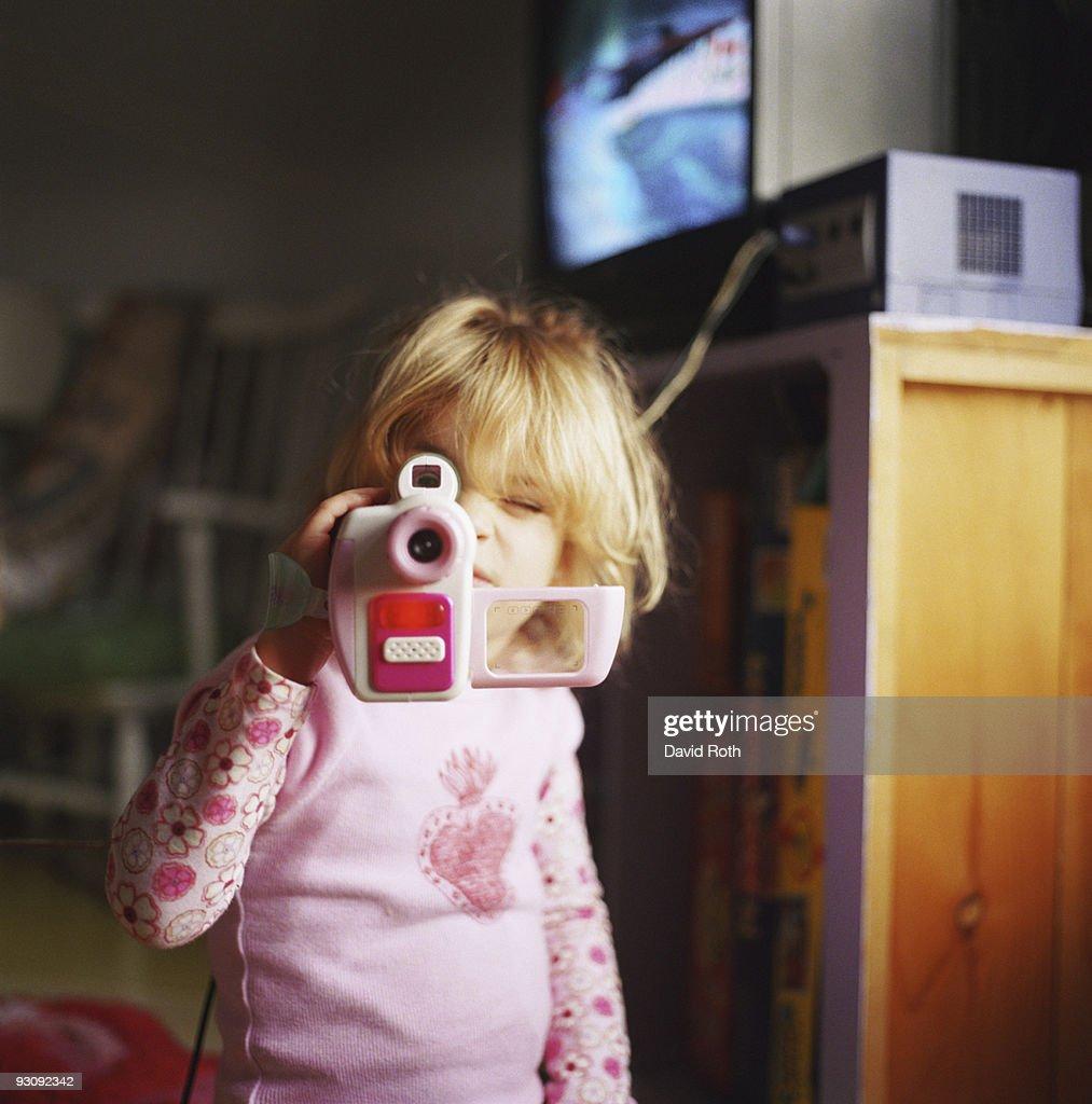Girl looking through toy camera