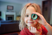 Girl looking through toy telescope