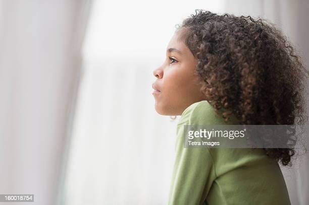 Girl (6-7) looking through window