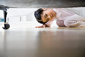 Girl (3-5) looking under bed, ground view