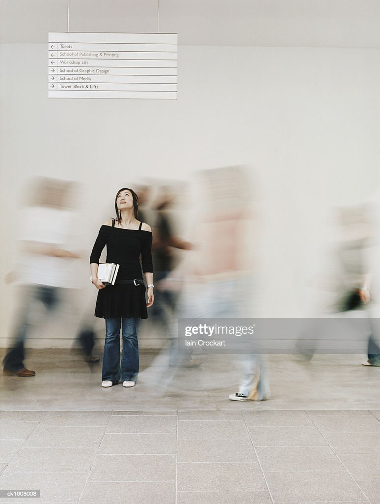 Girl Looking up at a Sign With People Rushing Behind Her : Stock Photo