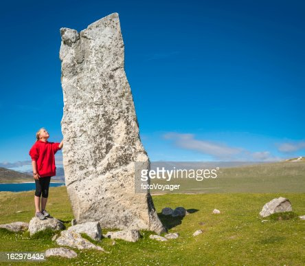 Girl looking up at ancient stone monolith Outer Hebrides Scotland