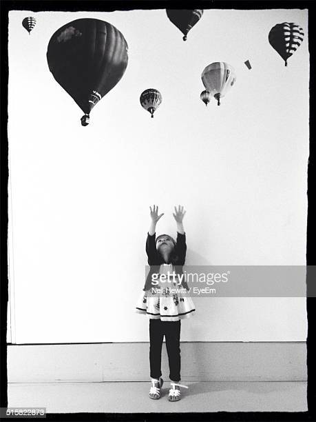 Girl Looking Up At Hot Air Balloons