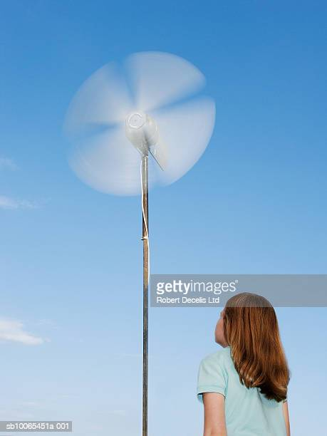 Girl (6-7) looking up at small wind turbine, low angle view