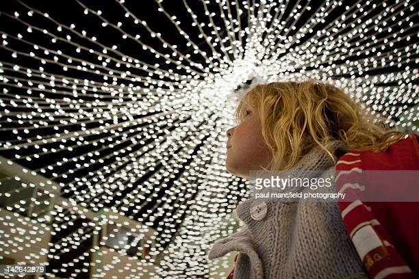 Girl looking upwards at fairy lights