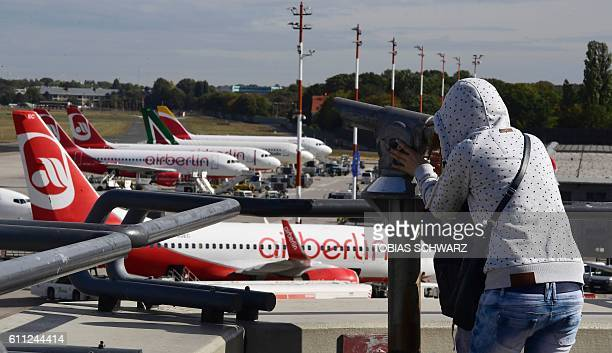 A girl looks at a plane of German airline Air Berlin and other aircrafts parked at the Tegel airport in Berlin on September 29 2016 Struggling Air...