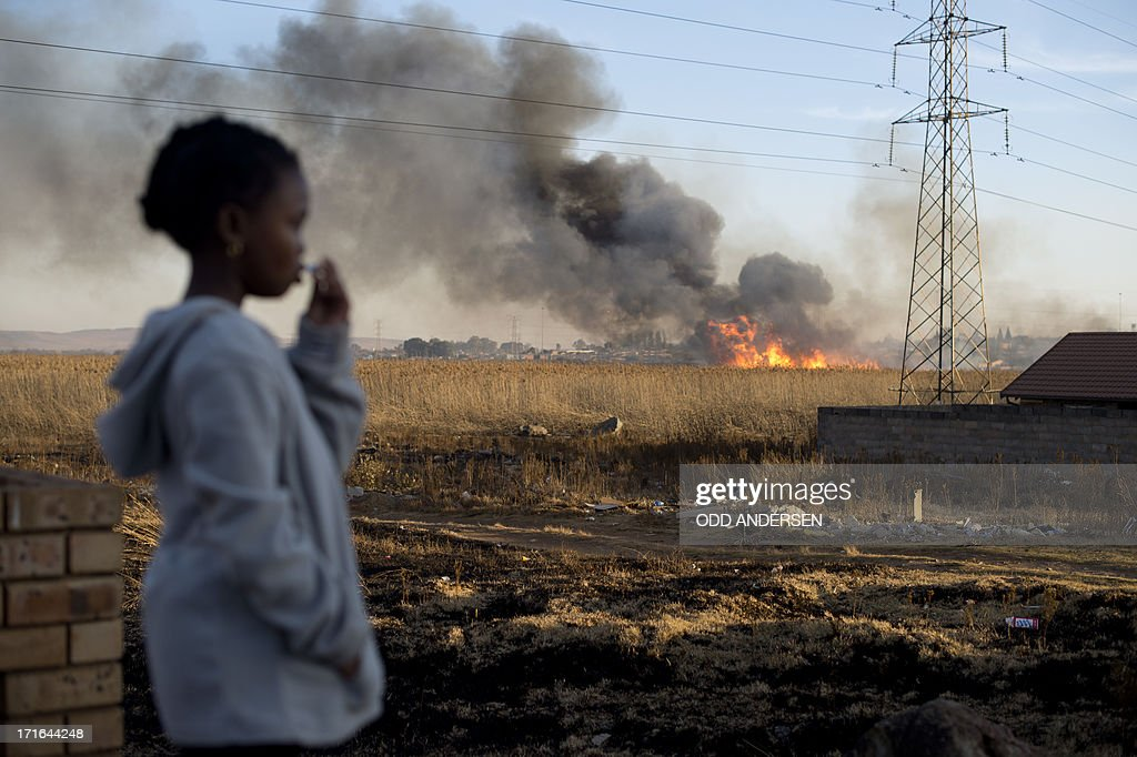 A girl looks at a veld fire in the township of Soweto on June 27 2013 The dry winter season see those veld firews erupt on a regular basis and...