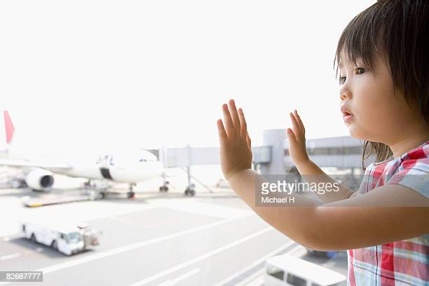 A girl looks at airplane from window in airport