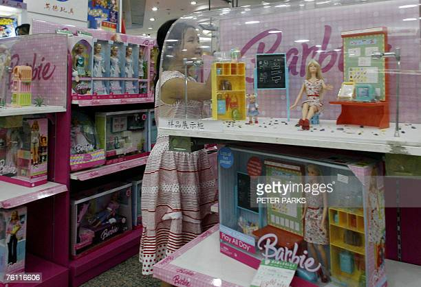 A girl looks at Barbie Dolls at a department store in Beijing 16 August 2007 China has hit out 16 August at the foreign press and 'irresponsible...