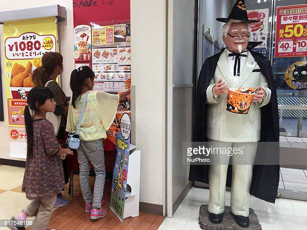A girl looks at Colonel Sanders of the Halloween version at a Kentucky Fried Chicken restaurant in Tokyo Japan 23 October 2016