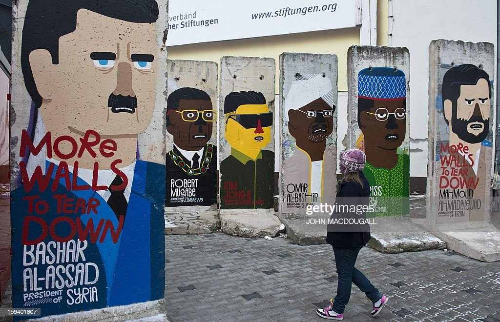 A girl looks at concrete slabs from the former Berlin wall decorated with likenesses of (from R) Iranian President Mahmoud Ahmadinejad , Chad's President Idriss Deby, Sudan's President Omar Al-Bashir, former North Korean leader Kim Jong-il, Zimbabwe's President Robert Mugabe, and Syrian President Bashar al-Assad, by French artist Guillaume Kashima, near the city's Checkpoint Charlie area in Berlin on January 13, 2013.