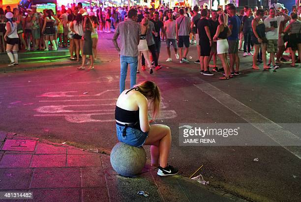 A girl looks down as she sits on a bollard of crowded Punta Ballena street in Magaluf holiday resort in Calvia on the Spanish Mallorca Island on July...