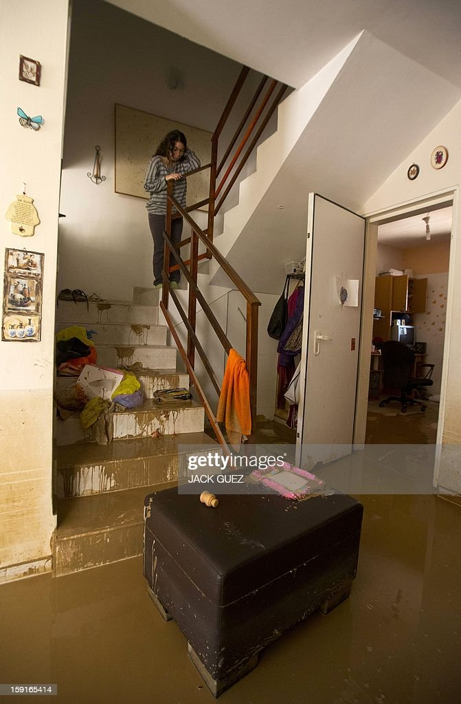 A girl looks down at flooding on the ground floor of her house in Beit Hefer near the Mediterranean coastal city of Netanya, north of Tel Aviv, on January 9, 2013, caused by heavy rains overnight. Israel and the Palestinian territories have been lashed by heavy rain and high winds since January 6, which has caused flooding across the region. AFP PHOTO / JACK GUEZ