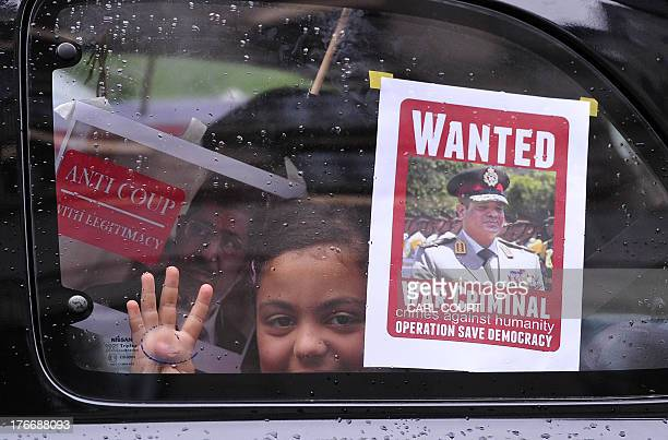 A girl looks from a car window with a 'wanted' poster of Abdel Fattah alSisi the army chief who ousted Egypt's Islamist president Mohamed Morsi as...