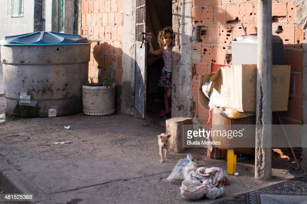 A girl looks from a door during a police operation at the Mare slums complex one of the largest 'favela' complexes in Rio on March 30 2014 in Rio de...