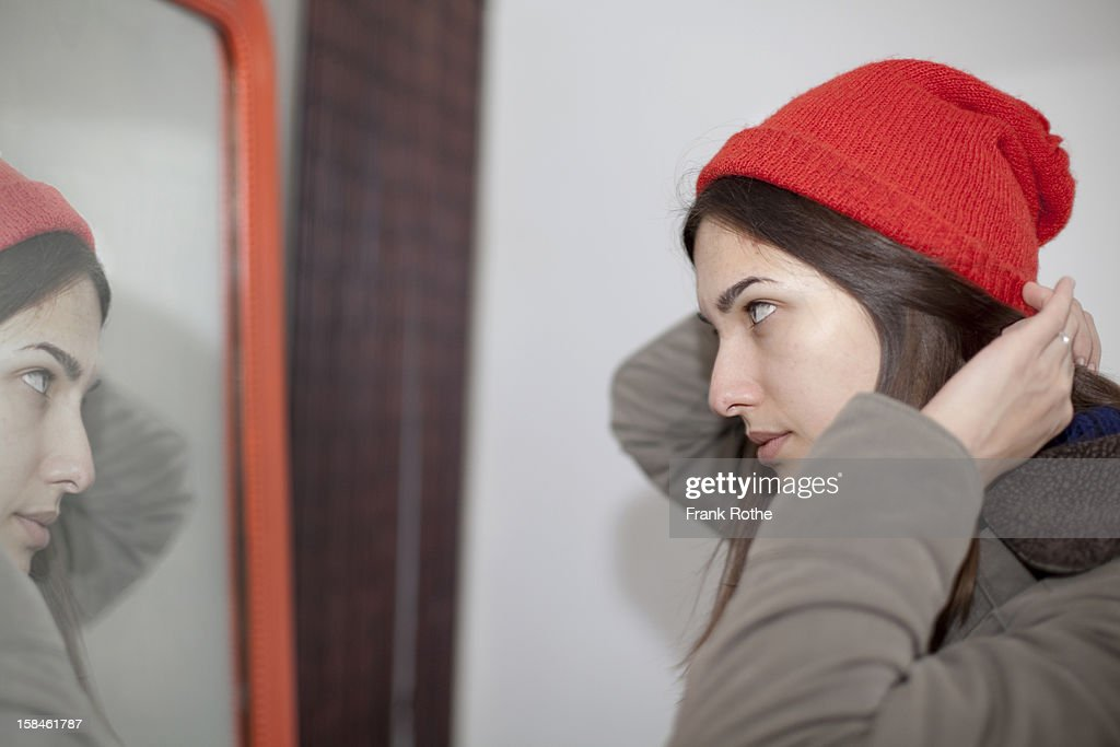 girl looks into mirror before she leaves the house : Stock Photo