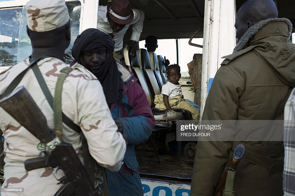 A girl looks on as Malian army soldiers control people coming from the North at a checkpoint in Niono, on January 18, 2013. France now has 1,800 troops on the ground in Mali, inching closer to the goal of 2,500 it plans to deploy in its African former colony, Defence Minister Jean-Yves Le Drian said today. That was 400 more than a day earlier, said the minister as he met with French special forces in the western port of Lorient. The troops have been sent to help the Malian army regain control of the north from Islamist groups.