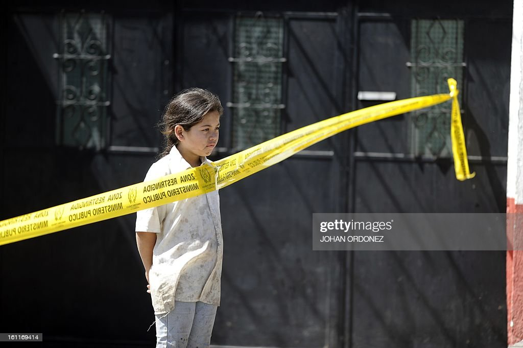 A girl looks on at a crime scene in downtown Guatemala City on Febrary 9, 2013. A vehicle was attacked by unidentified gunmen while traveling toward a prison; leaving two prison guards and a woman dead, authorities stated. AFP PHOTO/Johan ORDONEZ