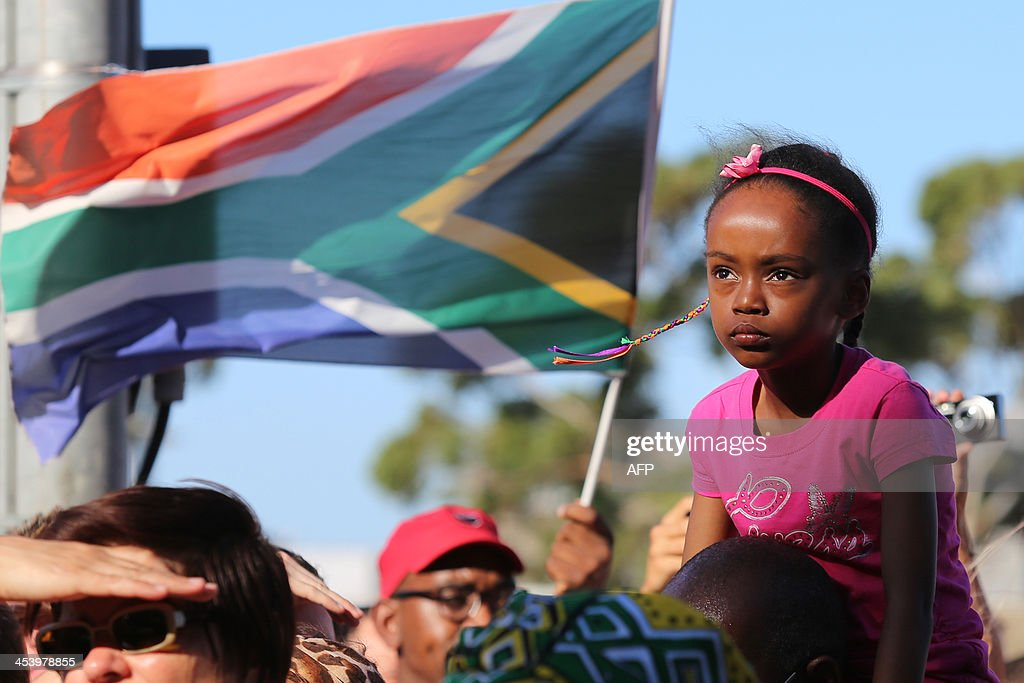 A girl looks on next to a man flying a South African flag as mourners gather to honour late South African former president Nelson Mandela at an inter-faith service on December 6, 2013, held at the Grand Parade in Cape Town, where Mandela made his first speech as a free man in 1990. Mandela, the revered icon of the anti-apartheid struggle in South Africa and one of the towering political figures of the 20th century, died in Johannesburg on December 5 at age 95. Mandela, who was elected South Africa's first black president after spending nearly three decades in prison, had been receiving treatment for a lung infection at his Johannesburg home since September, after three months in hospital in a critical state.