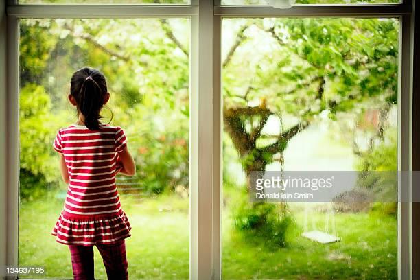 Girl looks out on wet garden