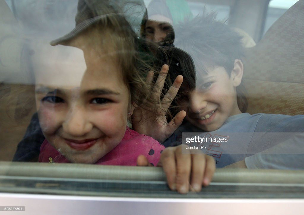 A girl looks out the window of a bus that will take her to a camp at the Jordanian military crossing point of Hadalat at the border with Syria after a long walk through the Syrian desert on May 4, 2016 in Hadalat, Jordan. Coming from the cities of Raqaa, Deir Al-Zor and Hama, roughly 300 hundred refugees crossed into Jordan at Hadalat on Wednesday, while over 5000 refugees crossed in the last four days coming from Aleppo.