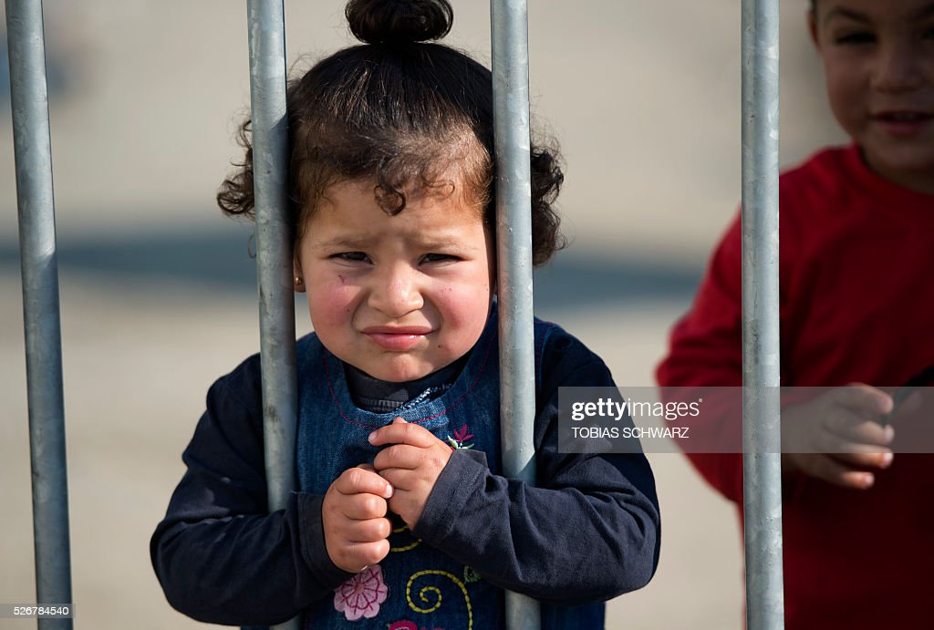 A girl looks through bars of a fence at a makeshift camp for migrants and refugees near the village of Idomeni not far from the Greek-Macedonian border on May 1, 2016. Some 54,000 people, many of them fleeing the war in Syria, have been stranded on Greek territory since the closure of the migrant route through the Balkans in February. / AFP / TOBIAS