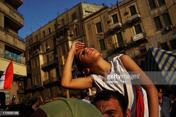 A girl looks up at fireworks as thousands of Egyptian protesters celebrate in Tahrir Square as the deadline given by the military to Egyptian...