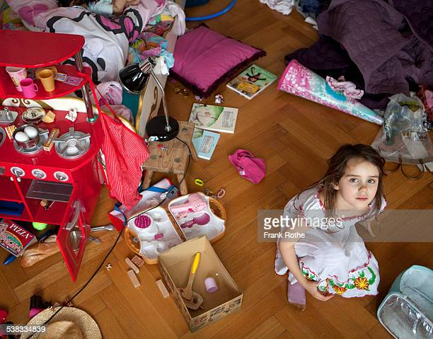 girl looks up while siting in here chaotic room