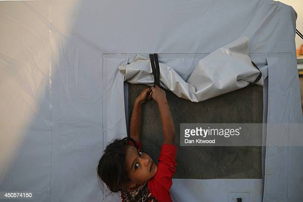 A girl lowers the flaps on a tent at a displacement camp set up next to a Kurdish checkpoint on June 13 2014 in Kalak Iraq Thousands of people have...