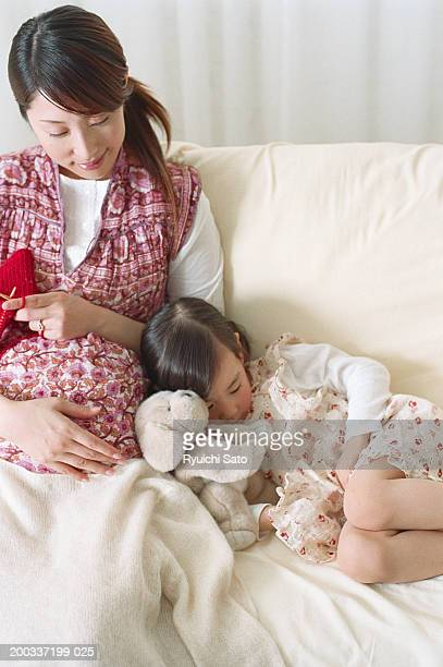 Girl (4-5) lying by pregnant woman on sofa