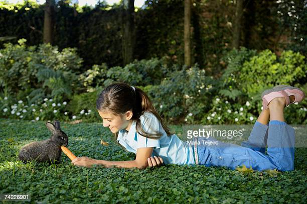 Girl (10-11) lying down on grass, feeding rabbit with carrot, side view