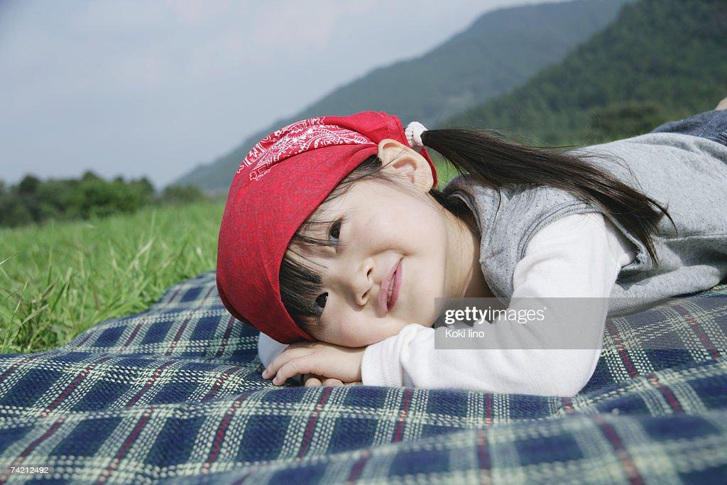 Girl lying down on picnic blanket : Stock Photo