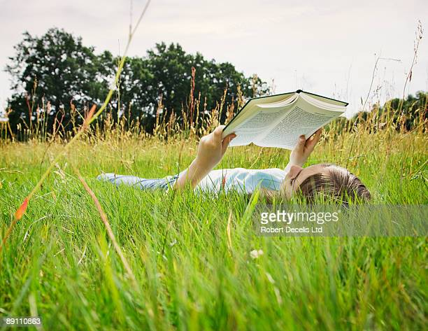 Girl lying down reading.
