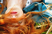 Redhead young girl lying in a meadow