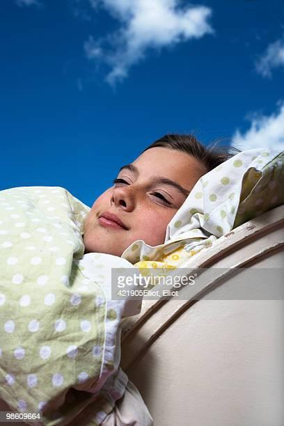 Girl lying in bed against a blue sky, Sweden.