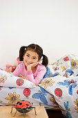 Girl (5-7) lying in bed