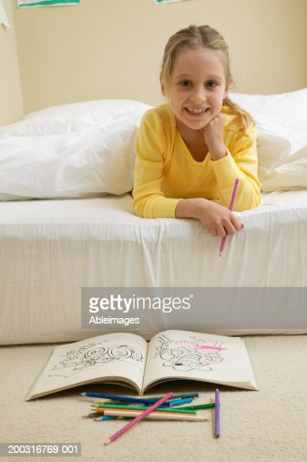 Girl (5-7) lying in bed with colouring in book on floor, portrait