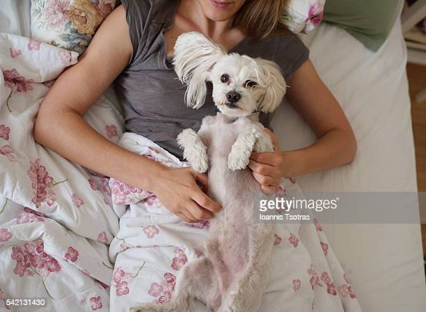 Girl lying in bed with her cute dog