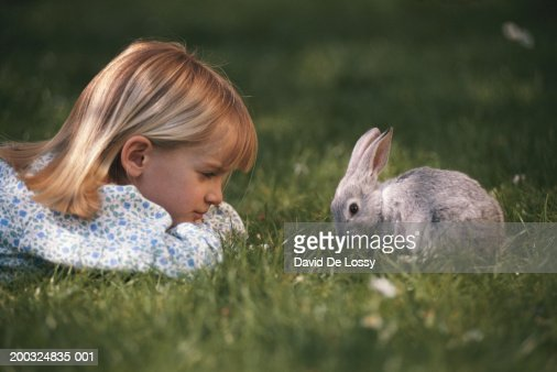 Girl (6-7) lying in field looking at rabbit, side view