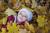 Girl lying in leaves in park