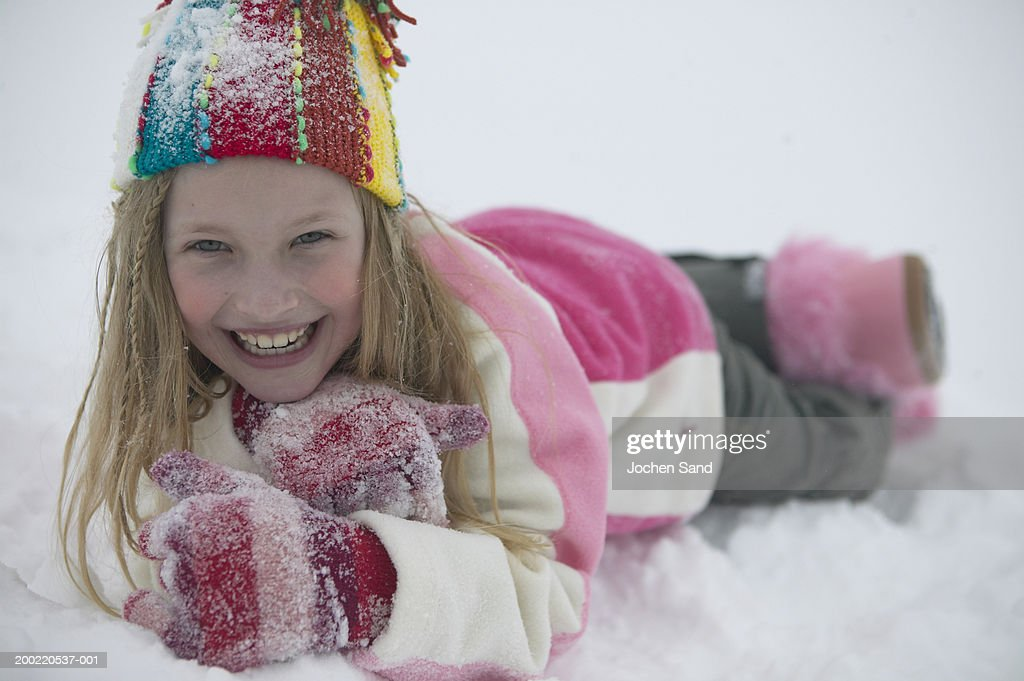 Girl (8-10) lying in snow, chin in hands, smiling, portrait