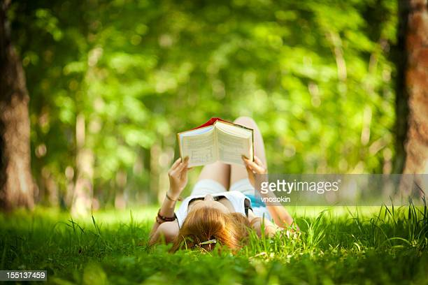 A girl lying in the grass while reading a book