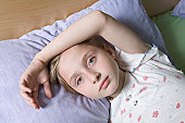 A girl lying on a bed, looking at camera