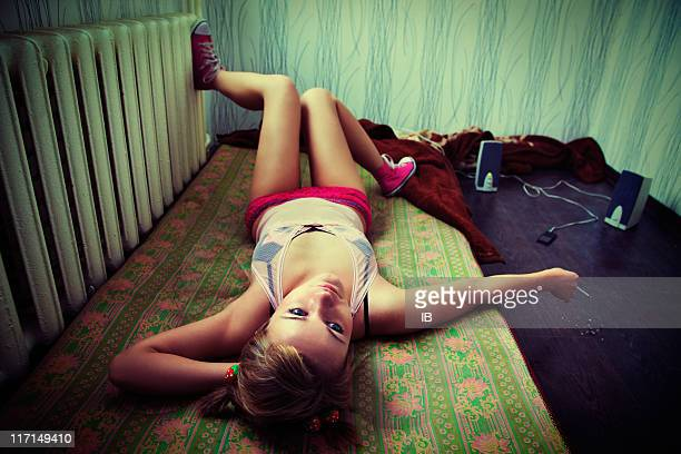 Girl lying on a mattress, smoking and listening to music