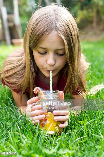 Girl lying on a meadow drinking infused water with various fruits