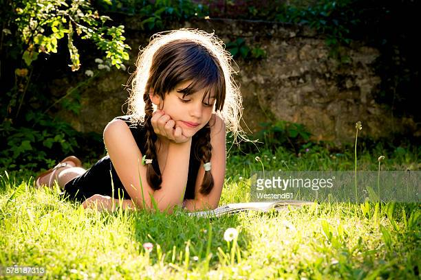 Girl lying on a meadow reading a book