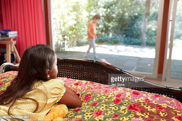 Girl (6-11) lying on bed and looking at boy through window